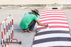 Worker using brush for painting white line on the road. The worker use brush for painting white line on the road for caution to reduce the car speed in Stock Image
