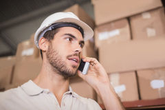 Worker using cellphone in warehouse Stock Photo