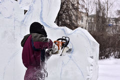 Worker using chainsaw carving an ice sculpture Stock Images