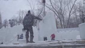 Worker using a chainsaw carving an ice sculpture. Men discuss work with ice sculptures. Workers clean the snow. Men stock video footage