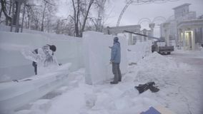Worker using a chainsaw carving an ice sculpture. Men discuss work with ice sculptures. Workers clean the snow. Men stock footage