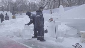 Worker using a chainsaw carving an ice sculpture. Men discuss work with ice sculptures. Workers clean the snow. Men stock video