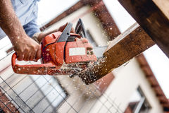 Worker using chainsaw for cutting timber wood, construction material, trimming and slicing logs Stock Image