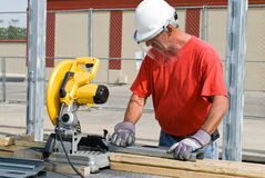 Worker using Chop Saw. Construction worker sawing pieces of metal stock photos