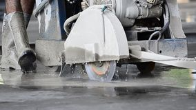 Worker using circular saw to cut concrete stock footage