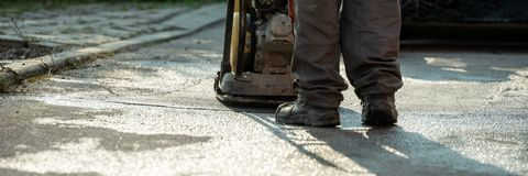 Worker using compactor to finish up patching a bump in the road royalty free stock images