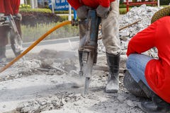 Worker using construction drilling cement on the ground Stock Images