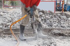 Worker using construction drilling cement on the ground Stock Photo