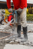 Worker using construction drilling cement on the ground Stock Photography