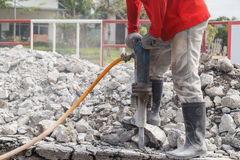 Worker using construction drilling cement on the ground Stock Photos