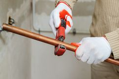 Installation of heating from copper pipes. The worker is using a copper pipe cutter to cut the pipes of the desired size stock photo