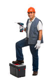 Worker using cordless electric drill. Full length portrait isolated worker using cordless electric drill and toolbox Royalty Free Stock Photo