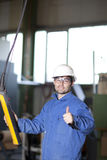 Worker using a crane. Blue collar worker using a crane in factory Royalty Free Stock Images