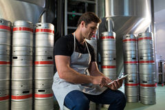 Worker using digital tablet while sitting on keg Royalty Free Stock Image
