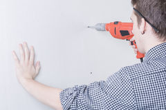 Worker using a drill. Construction worker using a drill - manual worker full portrait rear view Royalty Free Stock Images