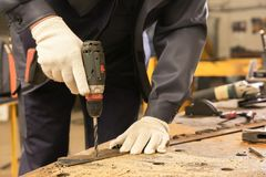Worker using drill for metalworking. At shop Royalty Free Stock Image