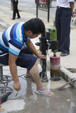Worker using drill on the road. Worker is using a drill on the street, Pingxing city China Royalty Free Stock Photos