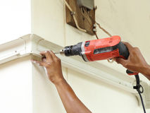 Worker using drill. To attach panel to wall Royalty Free Stock Photo