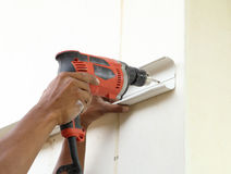 Worker using drill. To attach panel to wall Stock Images