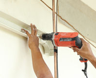 Worker using drill. To attach panel to wall Royalty Free Stock Photography