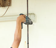 Worker using drill. To attach panel to wall Royalty Free Stock Photos