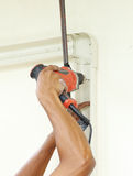 Worker using drill. To attach panel to wall Royalty Free Stock Image