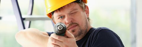Worker using electric drill portrait. Manual job, DIY inspiration, improvement, fix shop, yellow helmet, joinery startup idea, industrial education, profession Royalty Free Stock Images