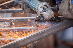 Worker using electric grinder machine cutting metal. Sparkles Stock Image