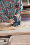 Worker Using Electric Planer On Wood. Midsection of worker using electric planer on wood at workshop Royalty Free Stock Photography