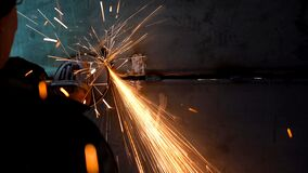 A worker using a grinder cut metal. Processing a metal product using a manual grinder