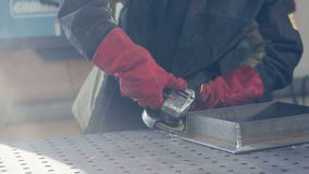Worker using grinder wearing red protective gloves, sparks.. Slow motion. stock video