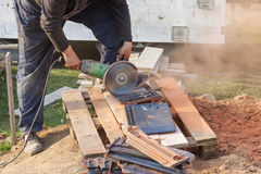 Worker using a hand circular saw to cut a roof-tile Stock Photo