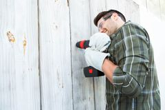 Worker using hand drill on wooden cabin. Side view of construction worker using hand drill on wooden cabin Royalty Free Stock Images