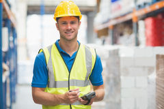 Worker using hand held computer. In warehouse Royalty Free Stock Image