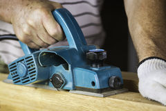 Worker using a hand planer Stock Images