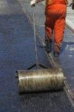 Worker using a hand roller for mastic asphalt paving Stock Image