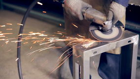 Worker using industrial grinder on metal parts in industrial plant, factory. stock footage