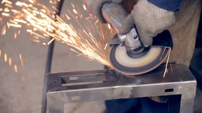 Worker using industrial grinder on metal parts in industrial plant, factory. stock video footage