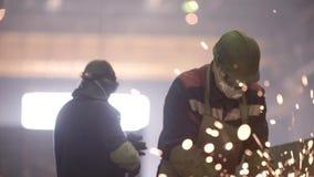 Worker using industrial grinder on metal parts in industrial workshop warehouse stock video footage