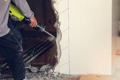 Worker using a jackhammer to drill into wall Royalty Free Stock Photography