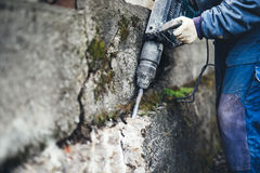 Worker using a jackhammer to drill into wall. professional worker in construction site Royalty Free Stock Photography