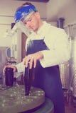 Worker using machine at wine factory Stock Photo