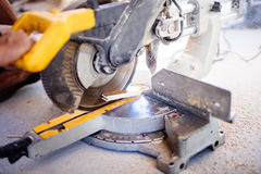 Worker using mitre saw for cutting wood parquet Stock Images