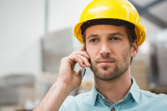 Worker using mobile phone in warehouse Stock Images