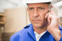 Worker using mobile phone in warehouse Royalty Free Stock Photo