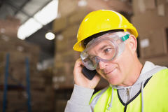 Worker using mobile phone in warehouse Stock Photo