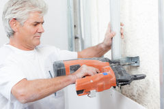 Worker using nail gun Royalty Free Stock Photo