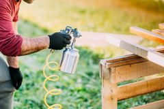 worker using paint gun or spray gun for applying paint on brown timber wood stock images