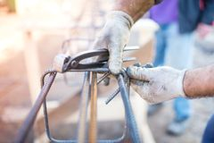 Worker using pincers and steel wire to secure bars for concrete pouring Royalty Free Stock Photos
