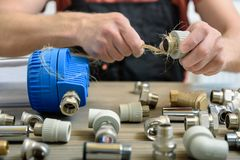 The worker is using a plumber`s hemp fibers. For sealing up pipe joints stock images